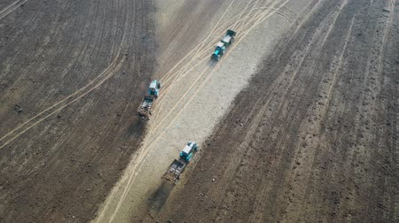 scatters : Tractors Drive On Agricultural Field And Fertilizing It With Manure Aerial Stock Footage