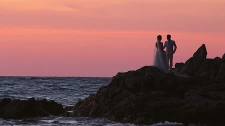 Married Asian couple silhouette with ocean rocks and sunset after wedding. Stock mozgókép