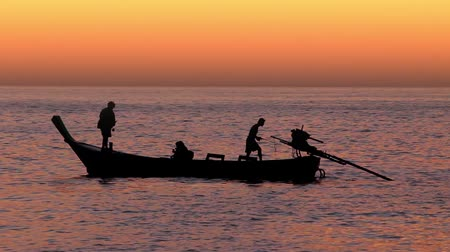 Fishermen silhouette in Thailand with evening sunset.