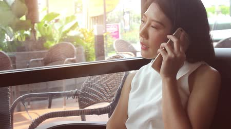 Asian woman talking on the phone casually at coffee shop.  White shirt and relaxing environment talking with friends on mobile device.