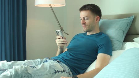 Young man waking up in bed and keeping communication and close contact on mobile device with friends and family or business contacts. Stock mozgókép