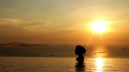 Sunset for freedom concept with woman in the water and beautiful silhouette.  Totally free and living a healthy life. Stock mozgókép