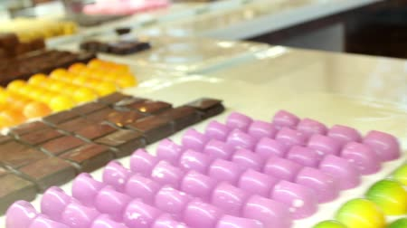 фиолетовый : Assorted chocolate candies in candy store with various colors and sizes.  Deliciouos chocolates with assorted colors for sale in candy shop.
