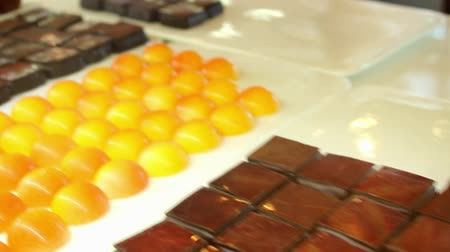 Assorted chocolates behind glass case at homemade sweets factory for the sweet tooth and candy lover.