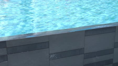 Swimming pool wall with aqua blue waves splashing over.  Pool planning and design for lifestyle and fitness. Stock mozgókép