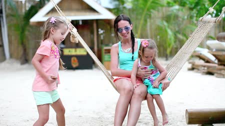 strand : Fashion mother and  her daughters relaxing in hammock in exotic resort