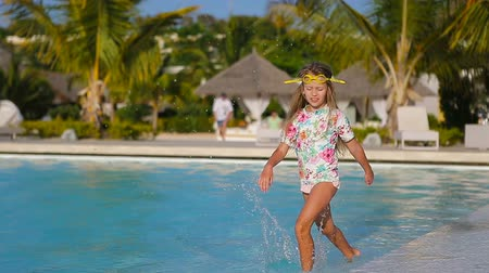 капелька : Little adorable girl in outdoor swimming pool