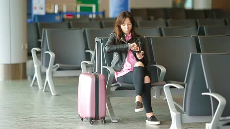 идущий : Airline passenger in an airport lounge waiting for flight aircraft. Caucasian woman with smartphone in the waiting room Стоковые видеозаписи