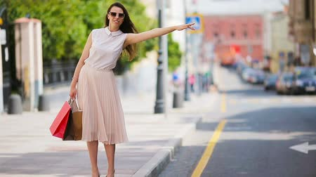 yaşam tarzı : Young happy girl with shopping bags catch a taxi. Portrait of a beautiful happy woman standing on the street holding shopping bags smiling and catching a taxi Stok Video