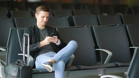 okos telefon : Urban business man talking on smart phone traveling inside in airport. Casual young businessman wearing suit jacket. Handsome male model. Young man with cellphone at the airport while waiting for boarding. Stock mozgókép