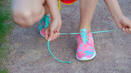 cipőfűző : Hands of a young woman lacing bright pink and blue sneakers. Running shoes - closeup of woman tying shoe laces.