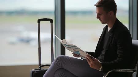 vypořádat se : Young caucasian man with newspaper at the airport while waiting for boarding. Casual young businessman wearing suit jacket. Dostupné videozáznamy