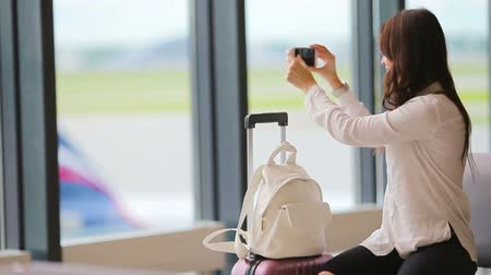 lounge : Airline passenger in an airport lounge waiting for flight aircraft and taking photo of airfield. Caucasian woman with smartphone in the waiting room