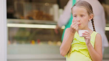 italian food : Adorable little girl eating ice-cream outdoors at summer. Cute kid enjoying real italian gelato near Gelateria in Rome Stock Footage