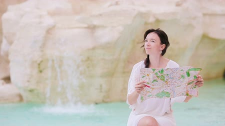 triton : Beautiful woman looking at touristic citymap near Trevi Fountain, Rome, Italy. Happy girl enjoy italian vacation holiday in Europe. Stock Footage