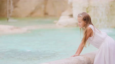 triton : Adorable little girl near the Fountain of Trevi in Rome. Happy kid enjoy their european vacation in Italy