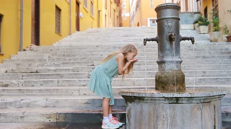 musluk : Little adorable girl drinking water from the tap outside at hot summer day in Rome, Italy Stok Video