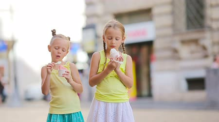 baunilha : Adorable little girls eating ice-cream outdoors at summer. Cute kids enjoying real italian gelato near Gelateria in Rome Stock Footage