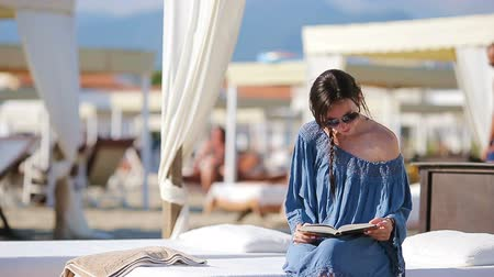 plážové lehátko : Young woman reading book during tropical beach vacation. Fashion girl read sitting in white sunbeds at european beach weekeend