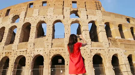 colosseo : Young woman taking photos in front of colosseum in Rome, Italy. Girl making photographs fo the memory of most popular destination in the world Stock Footage