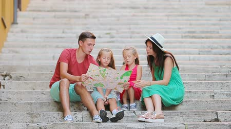 távozás : Family vacation in Europe. Parents and kids with touristic map searching the attractions.