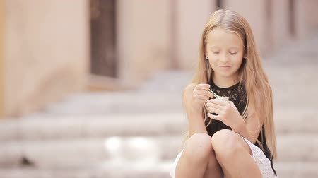 bonitinho : Adorable little girl eating ice-cream outdoors at summer. Cute kid enjoying real italian gelato in Rome