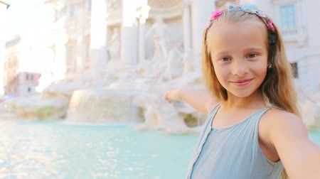 triton : Adorable little girl taking selfie background Trevi Fountain, Rome, Italy. Happy toodler kid enjoy italian vacation holiday in Europe.