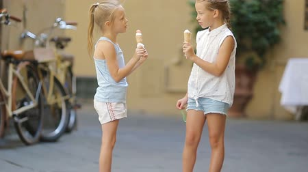 vaniglia : Adorable little girls eating ice-cream outdoors at summer. Cute kids enjoying real italian gelato near Gelateria in Rome Filmati Stock