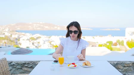 УВР : Beautiful elegant lady having breakfast at outdoor cafe with amazing view on Mykonos town. Woman drinking hot coffee on luxury hotel terrace with sea view at resort restaurant.