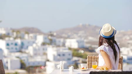УВР : Beautiful elegant girl having breakfast at outdoor cafe with amazing view on Mykonos town. Woman drinking hot coffee on luxury hotel terrace with sea view at resort restaurant. Стоковые видеозаписи