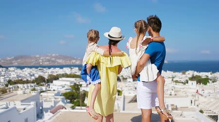 Санторини : Family in Europe. Parents and kids background the old town in Mykonos island, Greece