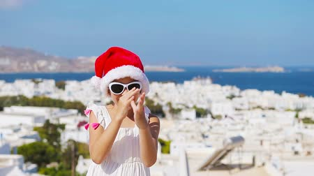 Киклады : Little funny girl in red Santa hat outdoors background of Mykonos. Стоковые видеозаписи