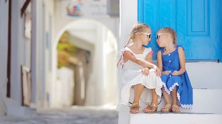 Санторини : Two girls in blue dresses having fun outdoors. Kids at street of typical greek traditional village with white walls and colorful doors on Mykonos Island, in Greece
