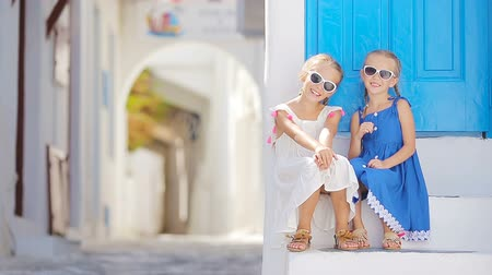 Киклады : Cute little girls at street of typical greek traditional village with white walls and colorful doors on Mykonos Island, in Greece Стоковые видеозаписи