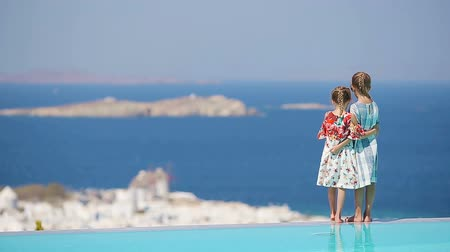 Киклады : Adorable little girls playing in the edge of outdoor swimming pool with amazing view of old Mykonos town, Europe