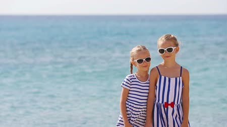 Киклады : Adorable little girls ooking at camera together during beach vacation. Kids enjoy summer vacation in greek beach