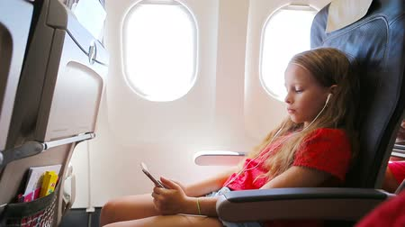 lugares sentados : Adorable little girl traveling by an airplane sitting near window. Kid listening music and sending message sitting near aircraft window