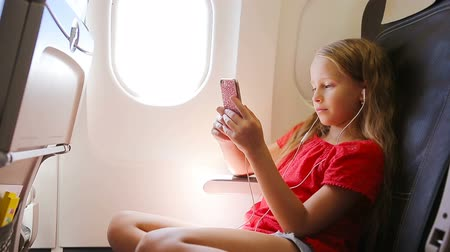 fasten : Adorable little girl traveling by an airplane sitting near window. Kid listening music sitting near aircraft window Stock Footage