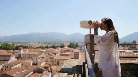 vigilância : Beautiful girl looking at coin operated binocular on terrace at small town in Tuscany, Italy