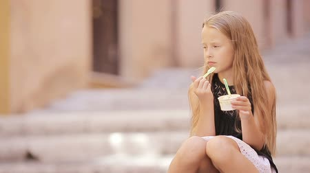 vanilya : Adorable girl eating ice-cream outdoors at european city. Cute kid enjoying real italian gelato in Rome Stok Video