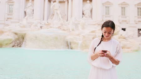 fontain : Young woman with smart phone at warm day outdoors in european city near famous Fontana di Trevi