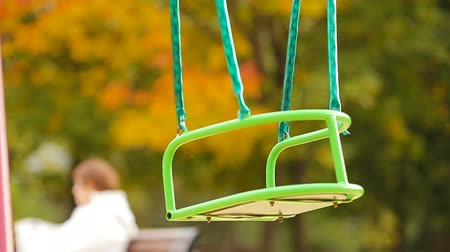 детская площадка : Closeup empty swing in autumn park outdoors