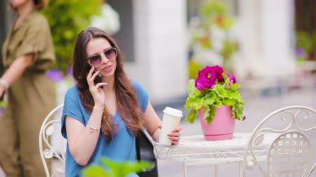 tea bag : Fashion happy girl talking by phone after shopping drinking coffee in open air cafe. Stock Footage