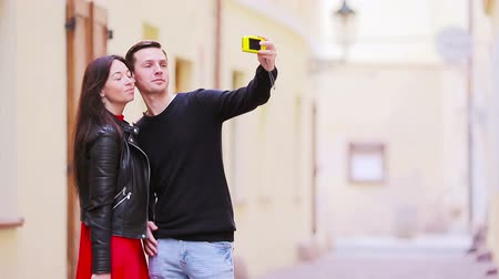 dospělí : Selfie photo by caucasian couple traveling in Europe. Romantic travel woman and man in love smiling happy taking self portrait outdoor during vacation holidays