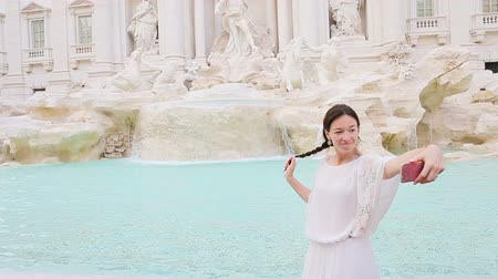 fontain : Young woman with smart phone taking selfie outdoors in european city near famous Fontana di Trevi