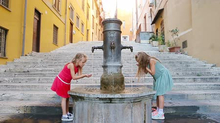 washing hands : Adorable girls drinking water from street fountain at hot summer day in Rome, Italy Stock Footage