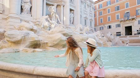 triton : Adorable little girls on the edge of Fountain of Trevi in Rome. Happy kids enjoy their european vacation in Italy