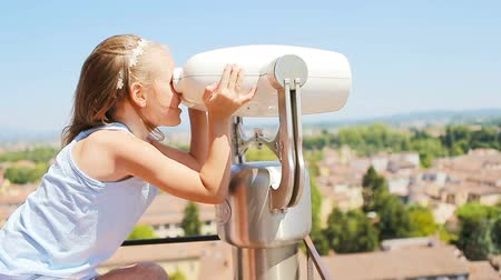 looking distance : Beautiful little girl looking at coin operated binocular on terrace at small town in Tuscany, Italy