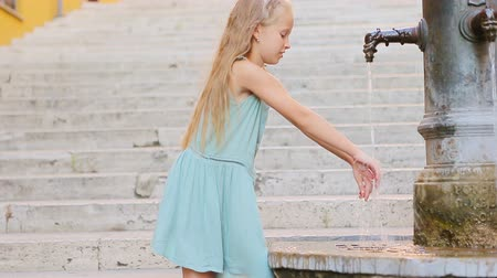 washing hands : Adorable girl drinking water from street fountain at hot summer day in Rome, Italy