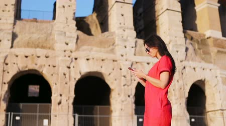 円形競​​技場 : Young woman in front of Colosseum with smart phone in hands in Rome, Italy. Girl in Europe vacation